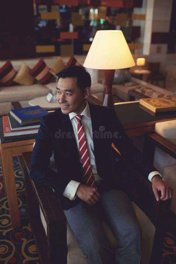 Intelligenter Geschäftsführer, der nachdem dem Treffen im Lehnsessel seines Privatbüroraumes sich entspannt lizenzfreie stockfotografie