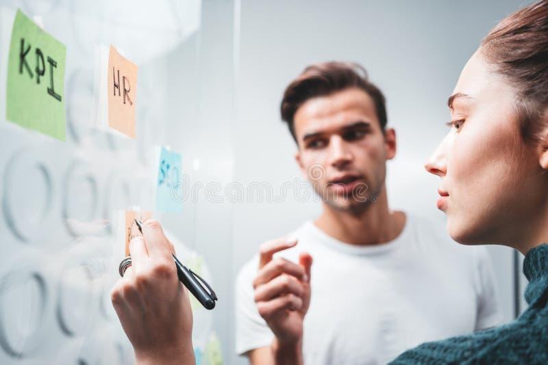 Intelligenter Geschäftsmann, der auf seine Kollegestellung hinter klebriger Glaswand hört stockfotografie