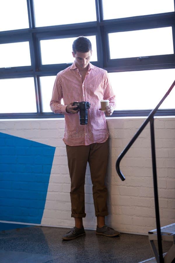 Intelligenter Geschäftsmann, der seine Kamera schaut stockbilder