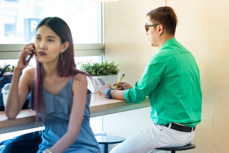 Intelligenter Handy und Stift des asiatischen Manngebrauches beim Sitzen im coffe stockfotografie