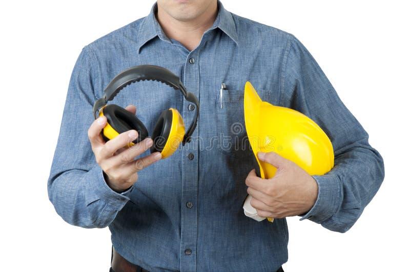 Intelligenter Ingenieur Worker blaues Hemd tragen und gelben Schutzhelm und gelbe Ohrmuffen auf Isolathintergrund halten lizenzfreie stockfotografie