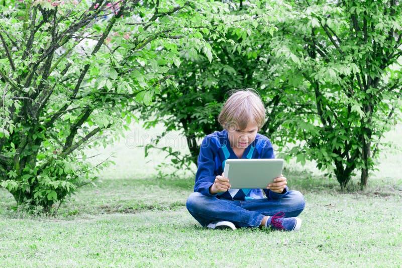 Intelligenter Junge, der draußen eine Tablette verwendet stockfoto