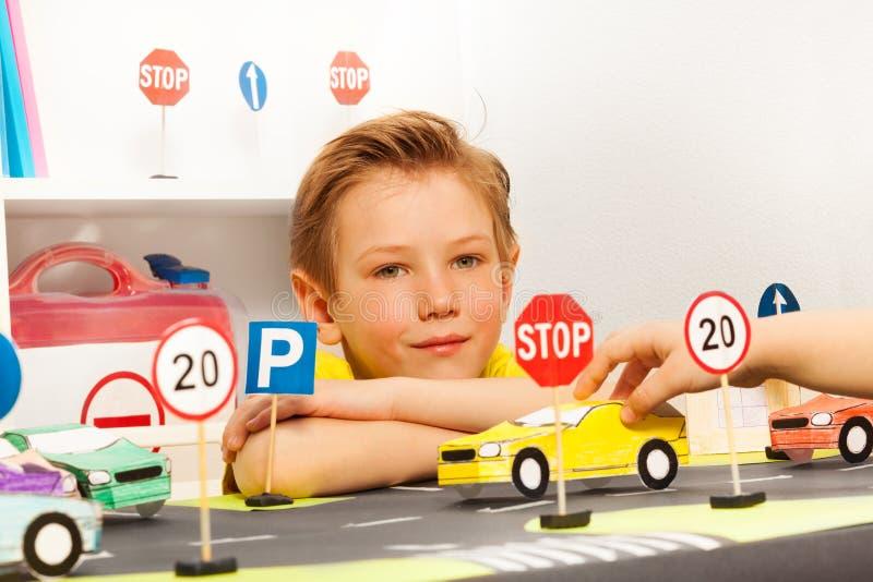 Intelligenter Junge, der am Straßenspielfeld sitzt lizenzfreies stockfoto