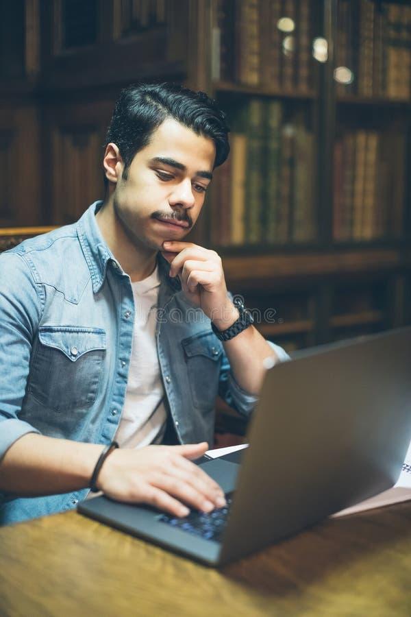 Intelligenter junger arabischer Mann, der in der Bibliothek mit Computer arbeitet stockbild