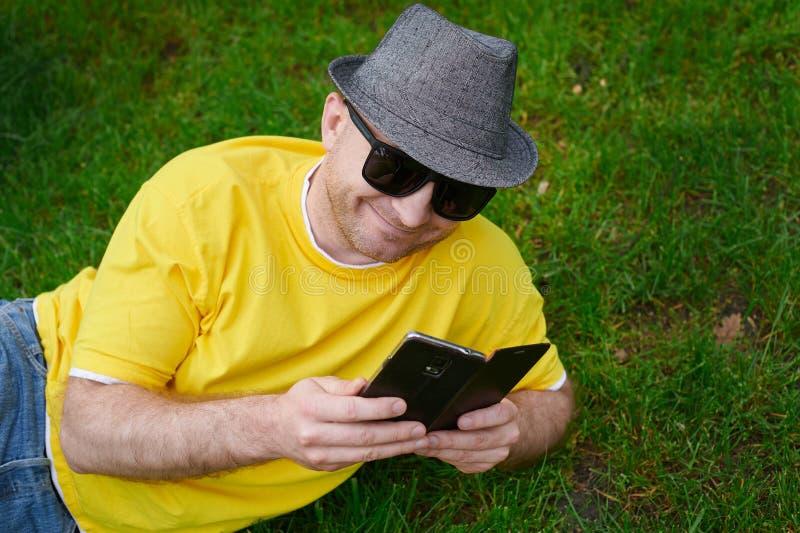 Intelligenter junger Mann in einem gelben T-Shirt mit dem Telefon auf dem Gras stockbilder