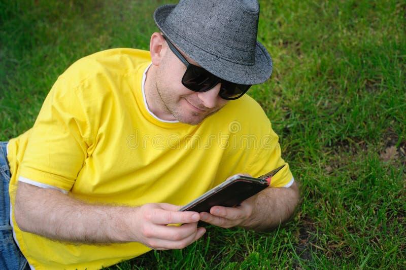 Intelligenter junger Mann in einem gelben T-Shirt mit dem Telefon auf dem Gras lizenzfreie stockbilder