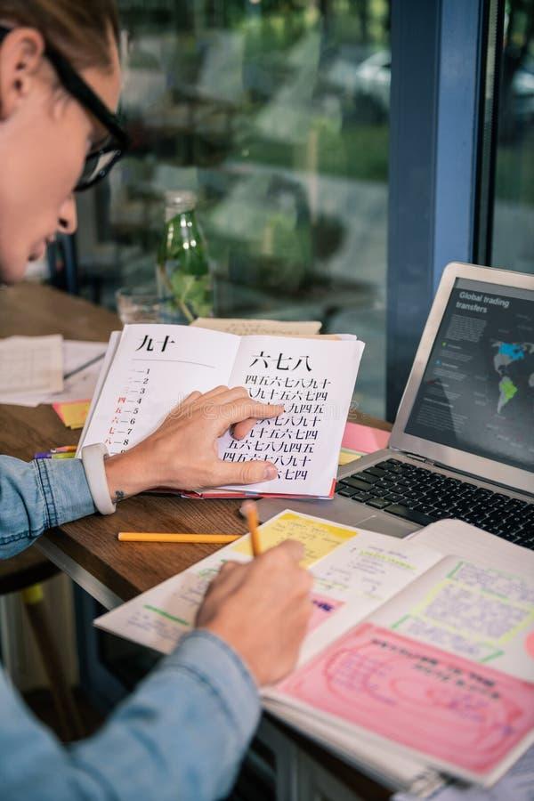 Intelligenter junger Student, der auf seine Aufgabe sich konzentriert stockfotos