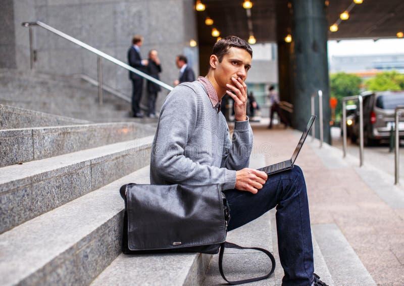 Intelligenter Kerl im grauen Hemd und in den Jeans stockfotografie