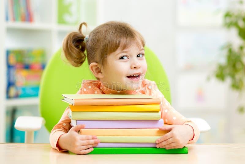 Intelligenter Kindermädchenvorschüler mit Büchern lizenzfreie stockfotos