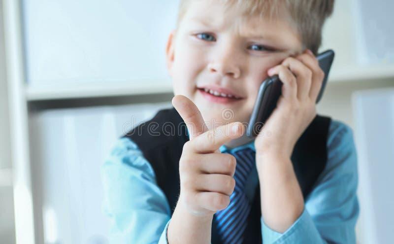 Intelligenter kleiner Junge in der Klage, die an Computer arbeitet, Kenntnisse nimmt und emotional am Telefon spricht stockfoto