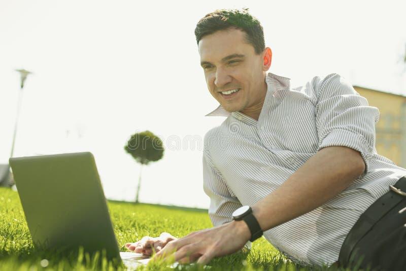 Intelligenter lächelnder Mann, der seine Arbeit im Park genießt lizenzfreies stockbild