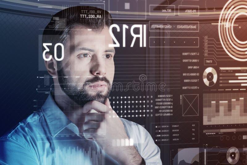Intelligenter Programmierer, der bei der Prüfung seines Programms interessiert schaut stockfotos