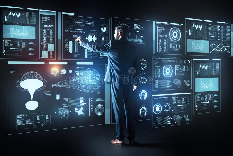 Intelligenter Programmierer, der den Schirm beim Arbeiten mit einem futuristischen Computer berührt stockfoto