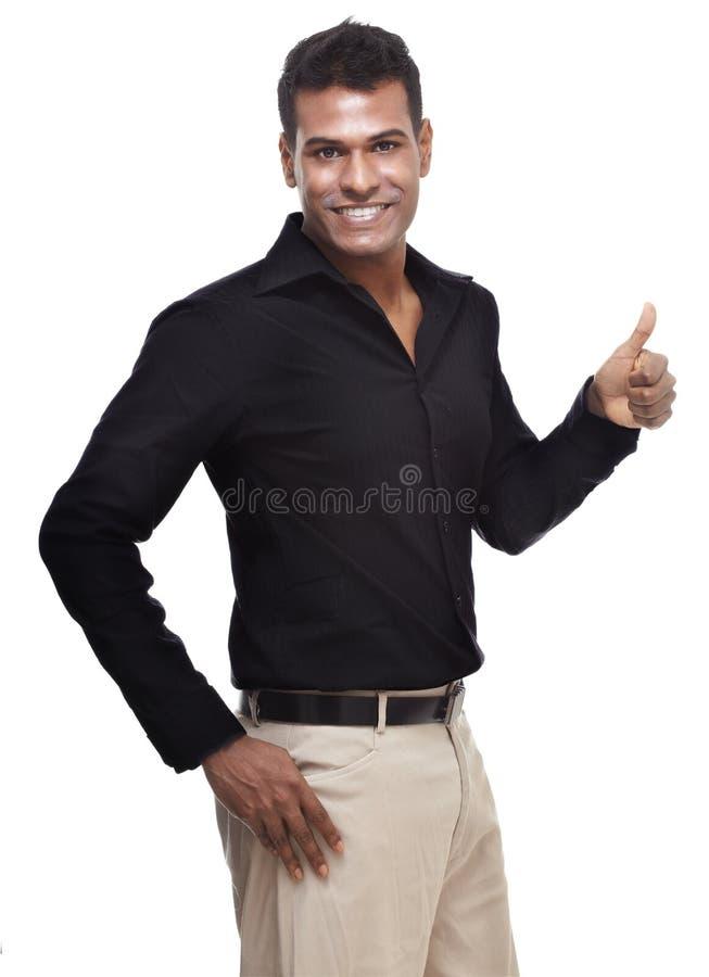 Intelligenter, stattlicher, junger indischer Mann, der Daumen aufgibt stockbilder