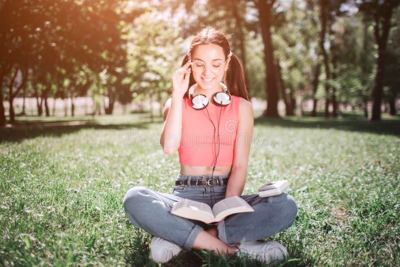 Intelligenter Student sitzt auf Gras im Park und liest ein Buch Sie sitzt mit ihren gekreuzten Beinen Mädchen hält ein lizenzfreie stockfotografie
