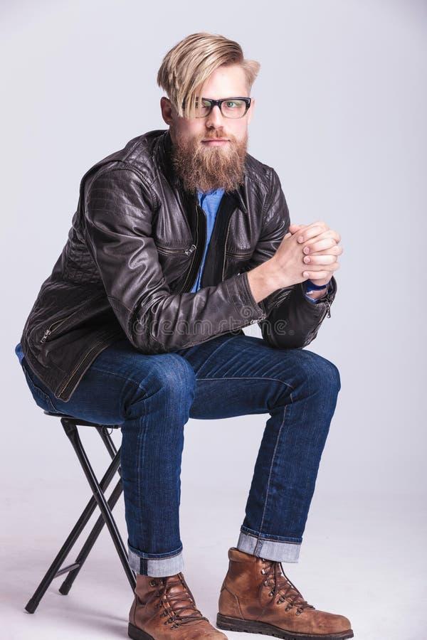 Intelligenter zufälliger blonder Mann, der auf einem Stuhl sitzt stockfotos