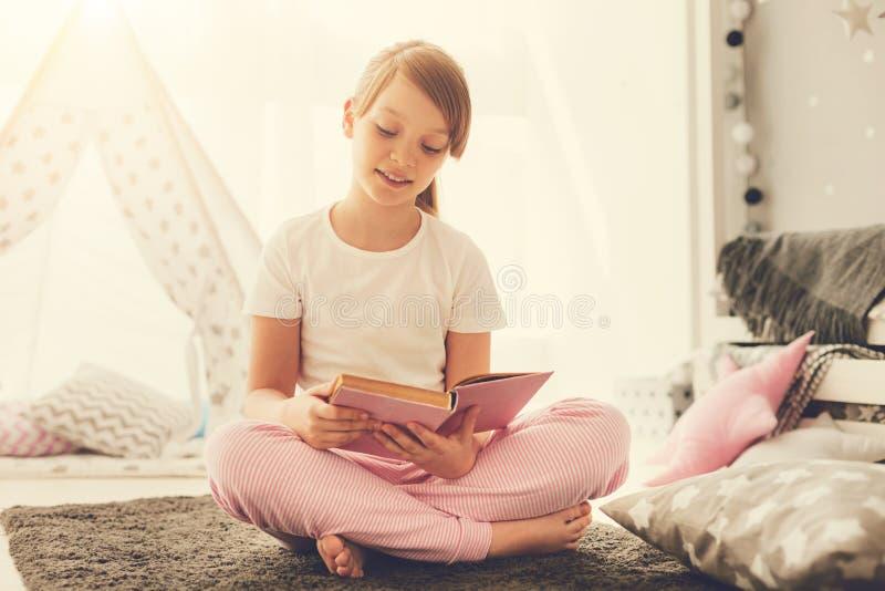 Intelligentes angenehmes Mädchen, das eine interessante Geschichte liest lizenzfreie stockfotos