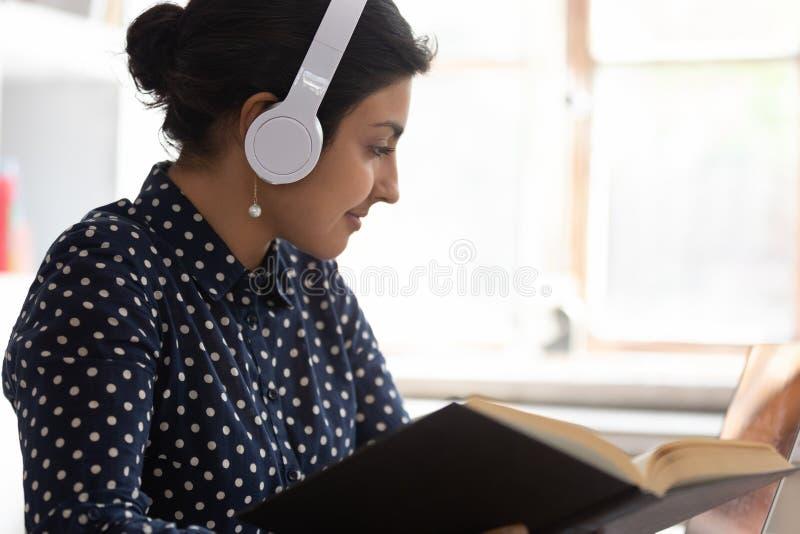 Intelligentes indisches Mädchen in den Kopfhörern studierend am Laptop lizenzfreie stockbilder