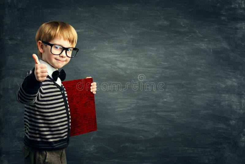 Intelligentes Kind in den Gläsern, Schulkind-Werbungs-Buch-Blinddeckel, Junge, der Daumen oben über Tafel zeigt stockbilder