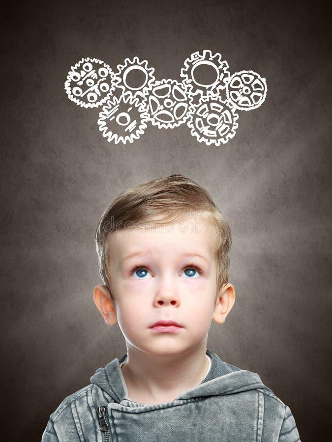 Intelligentes Kind denkt an das Betrachten von Gängen stockfotografie