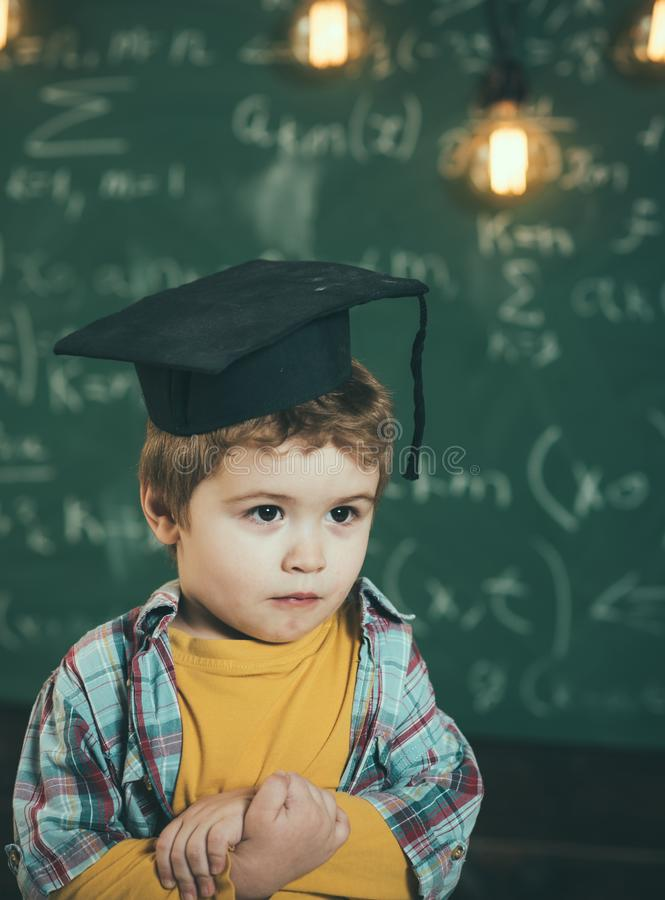Intelligentes Kind in der graduierten Kappe auf dem ernsten Gesicht, schüchtern, hält Hände gekreuzt Kind, Vorschüler oder erstes stockbild