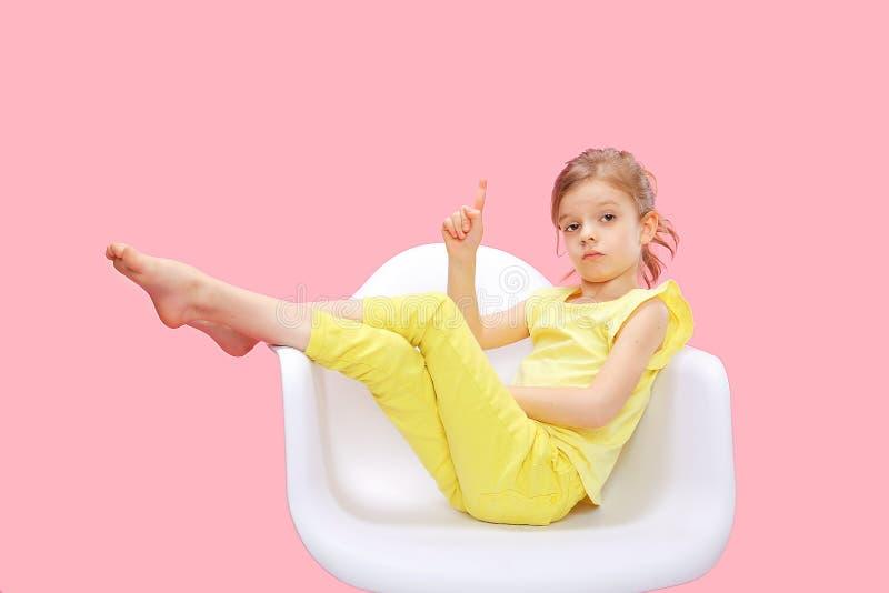 Intelligentes kleines Mädchen, das oben auf Rosa zeigt lizenzfreie stockfotografie