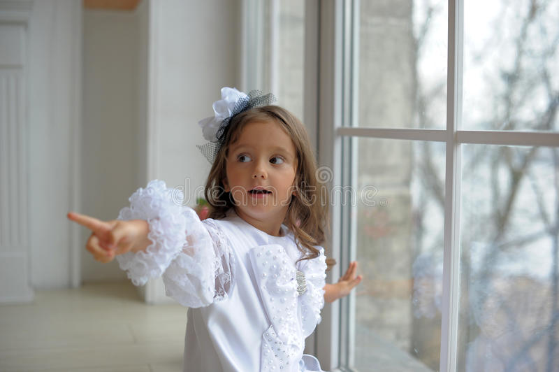 Intelligentes kleines Mädchen im weißen Kleid lizenzfreie stockfotografie