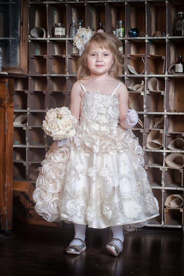 Intelligentes kleines Mädchen im weißen Kleid und in den Handschuhen lizenzfreies stockbild
