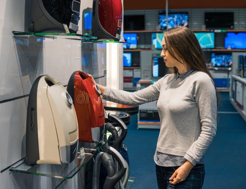 Intelligentes Kundenmädchen wählt neuen Staubsauger lizenzfreies stockbild