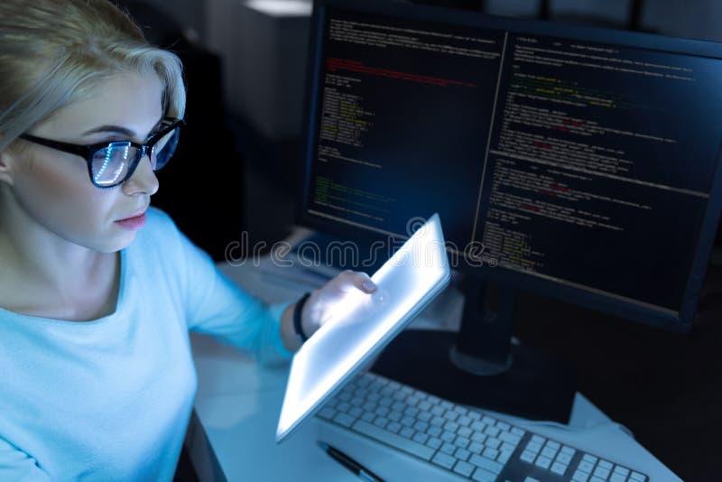 Intelligentes IT-Mädchen, das in der Dunkelheit arbeitet, beleuchtete Raum stockfotos