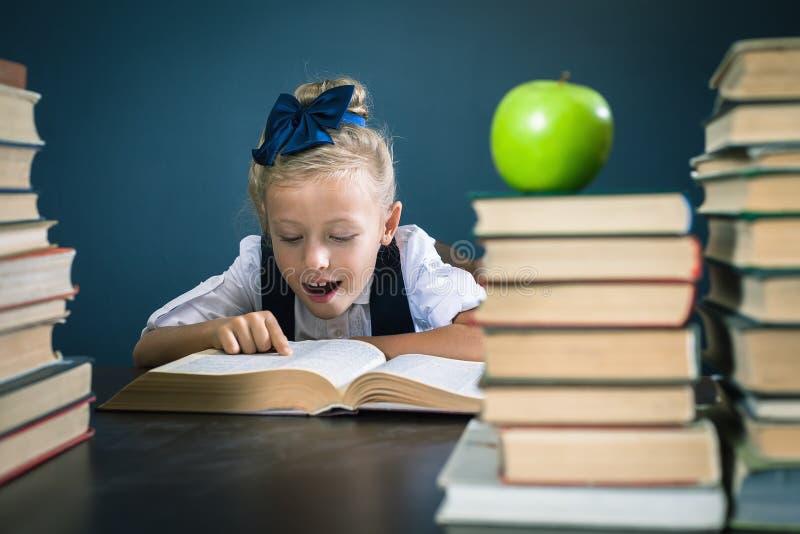 Intelligentes Schulmädchen, das ein Buch an der Bibliothek liest lizenzfreie stockfotografie