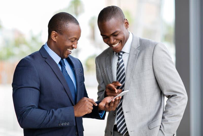 Intelligentes Telefon der afrikanischen Geschäftsmänner stockfotos