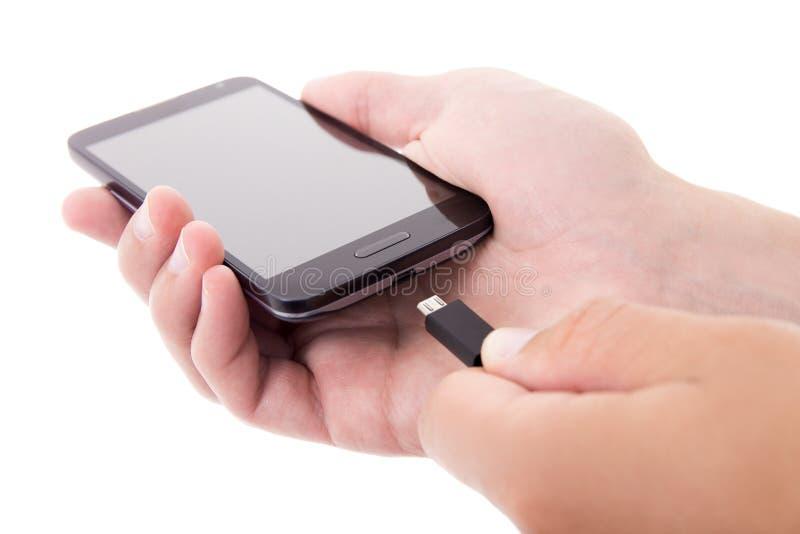 Intelligentes Telefon mit leerem Bildschirm und Ladegerät in den männlichen Händen lokalisiert stockfotos