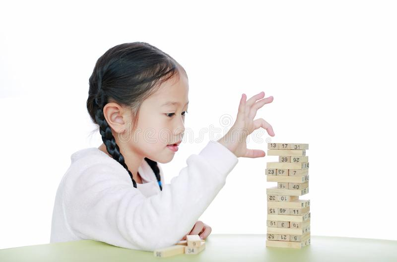 Intend little Asian child girl thinking to playing wood blocks tower game for Brain and Physical development skill in a classroom. Focus at children face. Kid stock photos