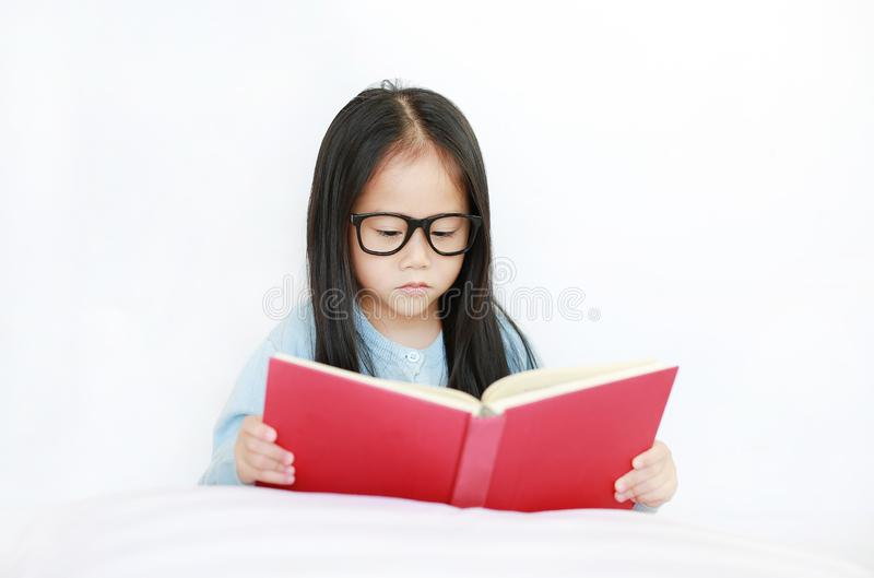 Intend little Asian kid girl wearing glasses reading hardcover book lying on bed against white background stock photo
