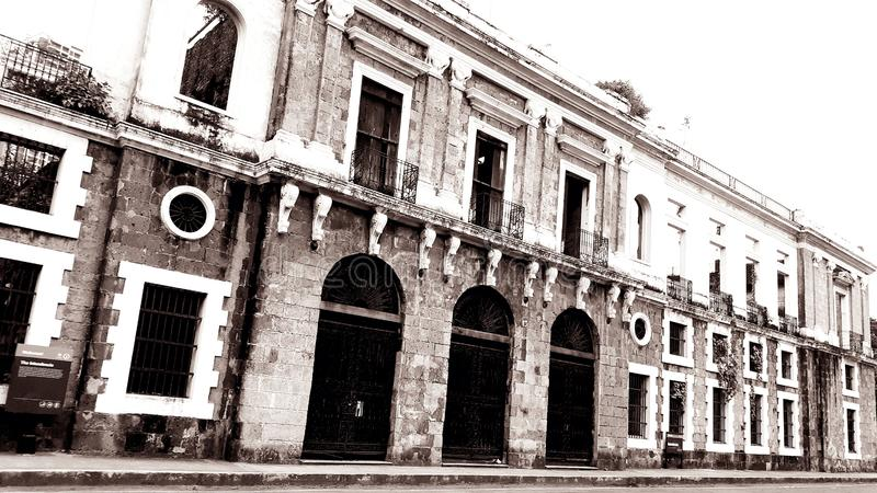The Intendencia - old colonial stucture in Manila, Philippines. Front, doors, windows, street, balcony, black, white, plants, sky royalty free stock images