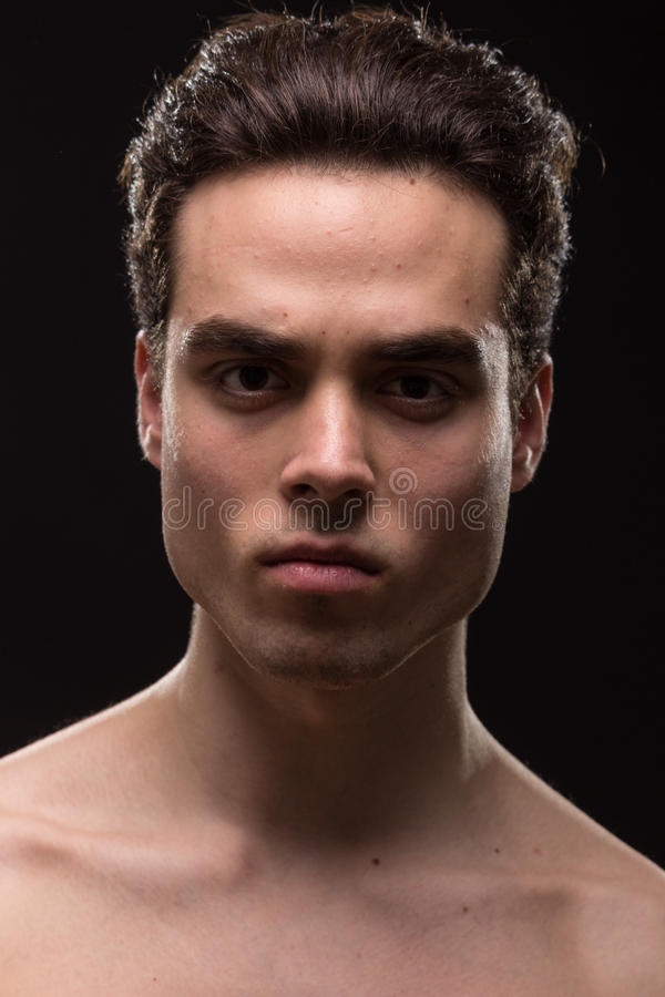 Intense angry young man head face closeup jawline. Intense angry young adult man model head face shoulders shirtless closeup jawline royalty free stock images
