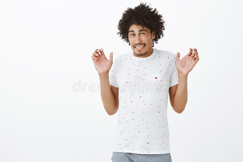 Intense guy feeling discomfort waiting for punishment. Portrait of displeased nervous cute hispanic guy in t-shirt. Raising palms in surrender and squinting stock photo