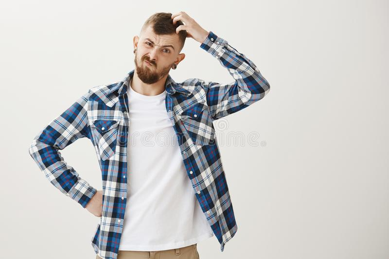 Intense male coworker trying solve issue, being clueless how to find solution. Frowning serious caucasian guy with beard royalty free stock photos