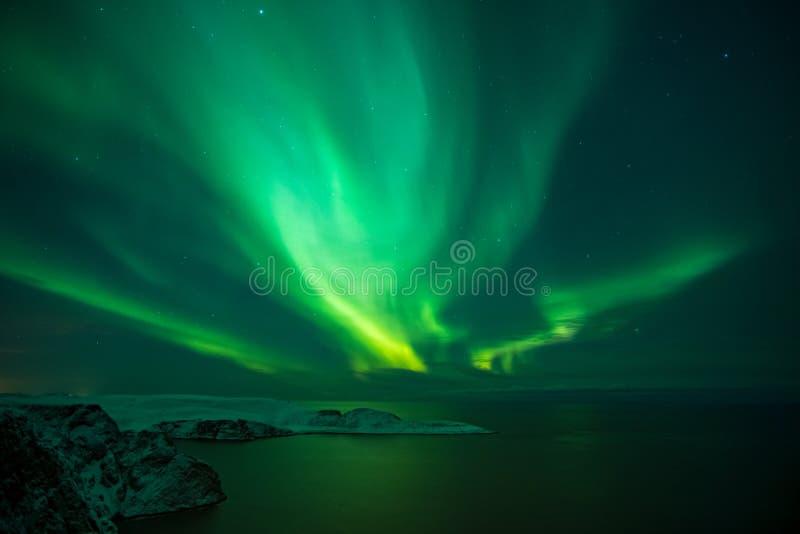 Intense northern lights, Aurora Borealis over Knivskjelloden Island, view from Nordkapp, North Cape, Norway. Intense northern lights, Aurora Borealis over royalty free stock photo