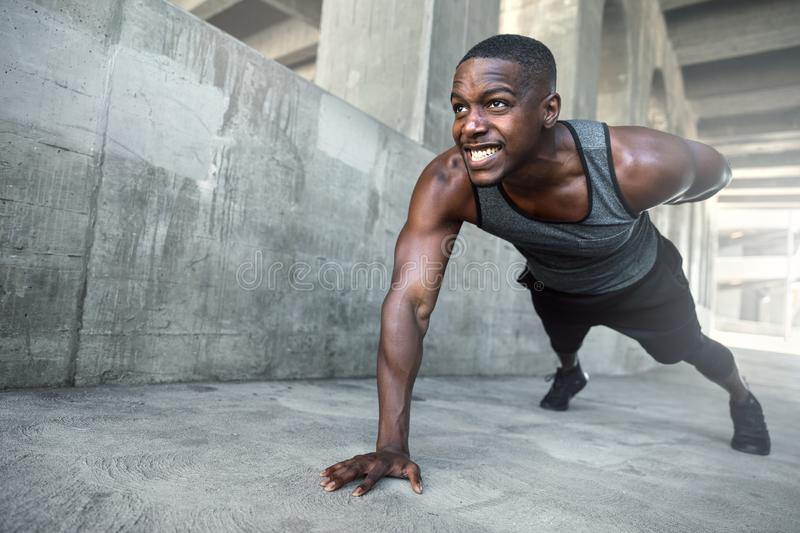 Intense push ups muscular male athlete training in city urban location, downtown city fitness lifestyle. Determined african american male athlete training in royalty free stock images