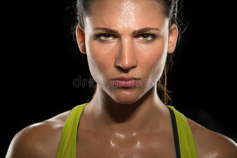 Intense stare eyes determined athlete champion glare head shot sweaty confident woman female powerful fighter close up. A powerful portrait of a physically royalty free stock photography