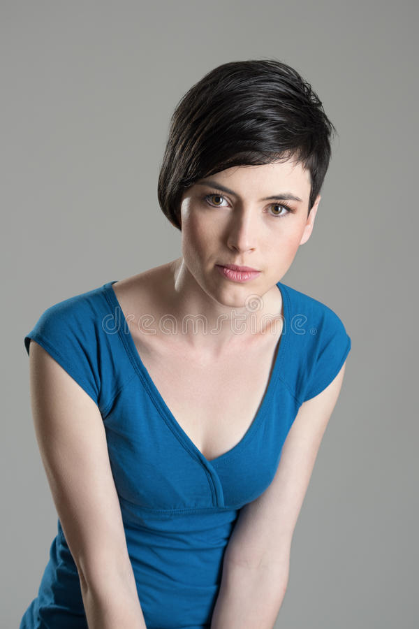 Intense studio portrait of young short hair beauty woman leaning towards and looking at camera royalty free stock photo