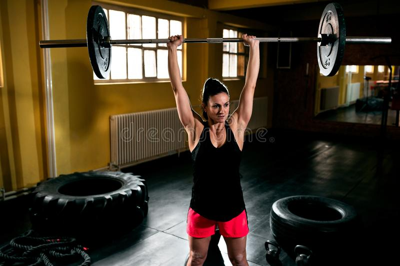 Bodybuilder woman doing exercise at gym. Intense workout in dark gym, bodybuilder woman doing exercise at gym stock images