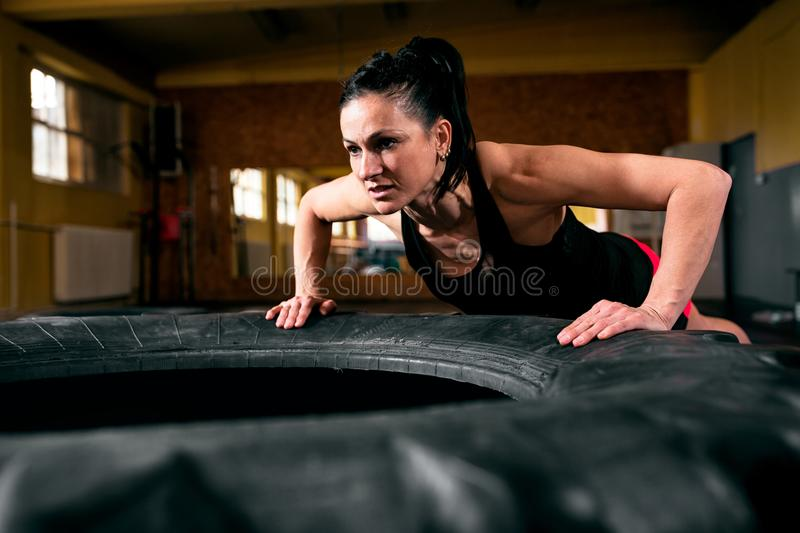 Intense workout in dark gym, strained young sports woma. N doing push ups on tire royalty free stock photos