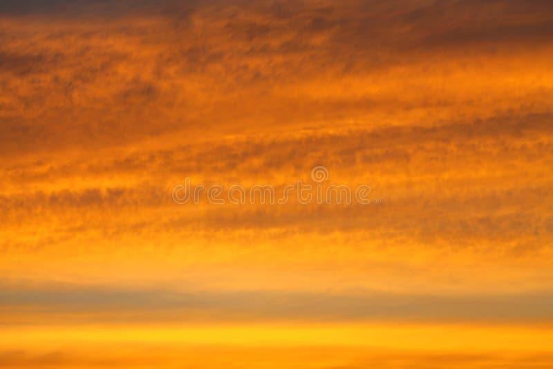Intensiv färgrik guld- himmel med lagret av molnet på aftonen för solnedgång arkivbilder