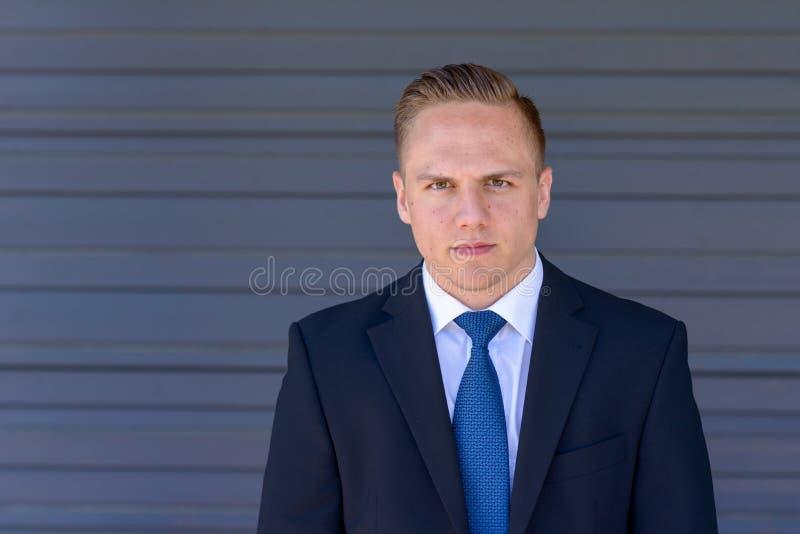Intensiv ung affärsman som stirrar på kameran arkivbild