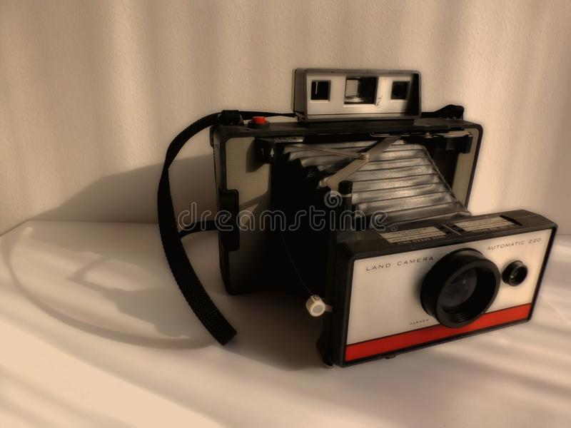 Blurred vintage old bellow type instant camera in antique tone style. Intentionally blurred soft presentation of vintage old bellow type instant camera in royalty free stock photography