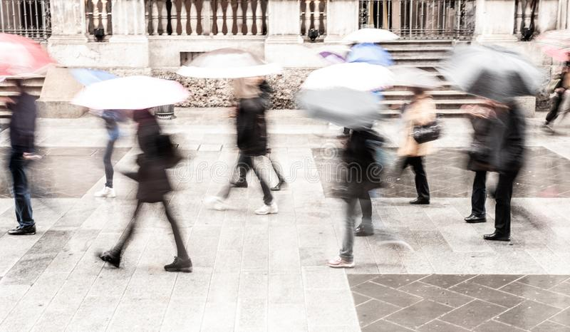 Intentionally motion blurred abstract image of commuters in a European city in a rainy day. royalty free stock photography