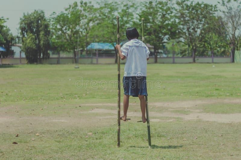 Intento del estudiante a caminar en las piernas de bambú, niños que juegan tha viejo imagen de archivo libre de regalías